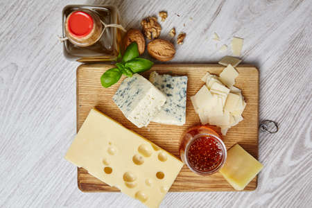 formagi: four cheeses with supplements on chopping board an white wooden table top view Stock Photo