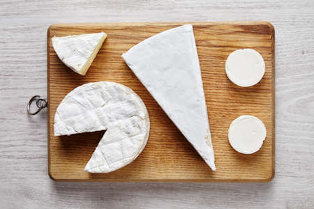 cheese plate: Avangard white soft cheeses: goat, brie, camembert on wooden desk on white table top view Stock Photo