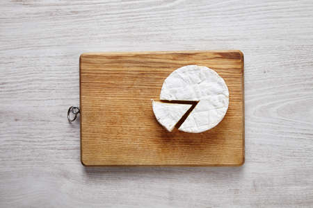 formagi: Splitted camembert cheese on chopping plate on white wooden table