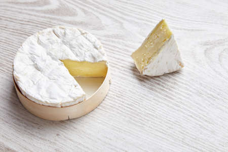formagi: Camembert with piece of it , isolated on white brushed farm table