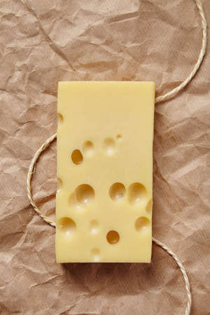 formagi: Emmental cheese isolated on craft brown paper with rope top view Stock Photo