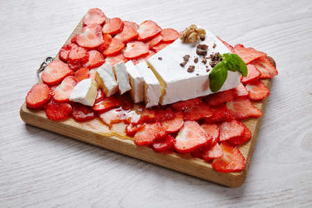 formagi: Diced strawberries with fresh brie and basil topped with honey on grunge white table