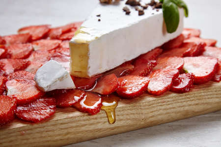 formagi: Sliced strawberries on wooden plate and fresh brie topped with honey close up Stock Photo