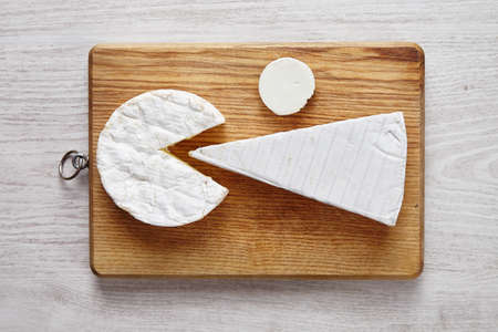 formagi: Modern cheese art on chopping plate on white wooden table
