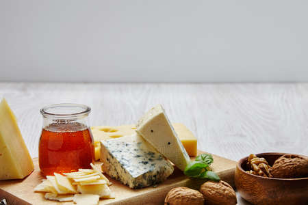 formagi: Cheese board with nuts basil and honey in front od display board Stock Photo