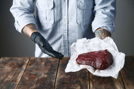 tattoed: Close up, tattoed hands in black gloves offers steak meat on camera