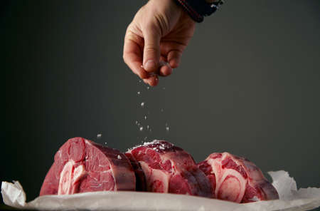 salt and pepper: Hand is satling three fresh meat steaks with bone
