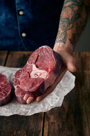 tattoed: Tattoed hand offers a piece of meat stake above two steaks on craft paper, close up