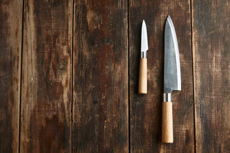Two old brushed knives big and small on wooden table Standard-Bild