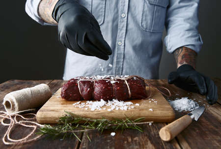 Tattoed butcher in black gloves salts tied piece of meat to smoke it.
