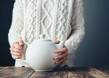 teapot: Woman in warm knitted thick sweater holds big white teapot with tea on grunge wooden table. Front view, anfas, no face. LANG_EVOIMAGES