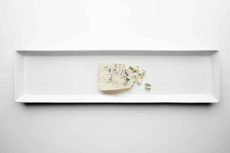 formagi: Piece of gorgonzola isolated on white plate top view. Roquefort or dor blue cheese as well.
