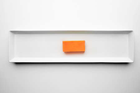 formagi: Orange brick of Cheddar cheese isolated on white plate, top view LANG_EVOIMAGES