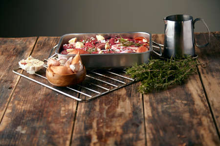 steel pan: Meat in steel pan with spices around: garlic, rosemary, onions; ready to cook on wooden table