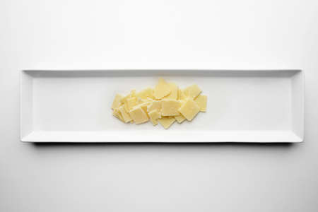 formagi: Square slices of parmesan isolated on white plate in center, top view.