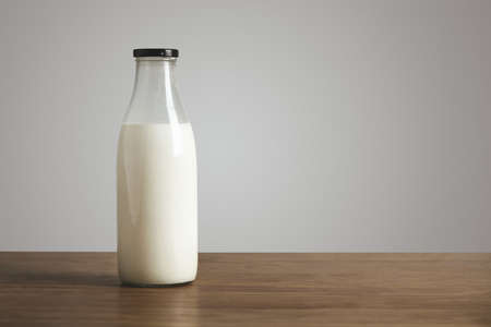 Simple vintage bottle filled with fresh milk on thick wooden table. Closed with black cap. Cafe shop