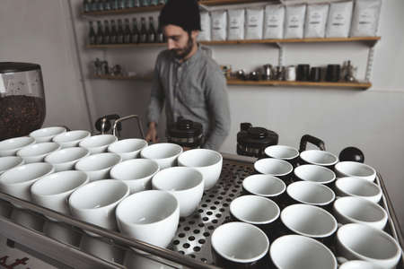 artisanal: Barista behind the big coffee machine with many empty white and black cups on top. Wide angle in cafe shop LANG_EVOIMAGES