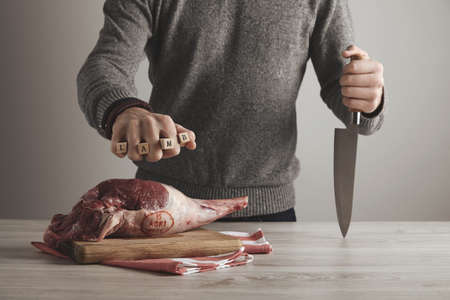 Man holds letters LAMB in fist and knife in other hand above the icelandic raw lamb leg meat flash stamped by veterinary control , isolated on blanck background. Paleo diet, organic food.