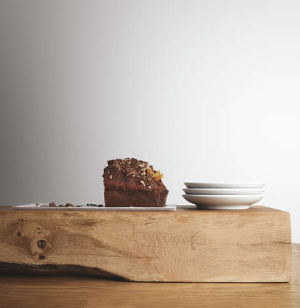 artisanal: Half of tasty chocolate cake with dried fruits on white long plate near three small blank tea dishes on wooden raw brick and thick table in cafe shop LANG_EVOIMAGES