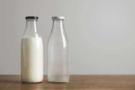 mleka: Proste zabytkowe butelki z świeżego mleka i puste na grubym drewnianym stole. Zamknięto czarną czapkę. sklep Cafe LANG_EVOIMAGES