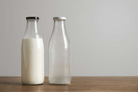 milk bottle: Simple vintage bottles with fresh milk and empty on thick wooden table. Closed with black cap. Cafe shop