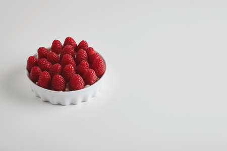 accurately: Heap of ripe raspberries accurately placed in ceramic bowl isolated on white table
