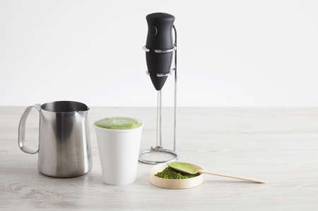 steel  milk: All necessary to prepare latte in modern way. Sale presentation. Electric milk froather on chrome stand, organic premium matcha tea powder japan, take away paper glass, steel milk pot for cappuccinator. All on wooden table isolated on simple background. LANG_EVOIMAGES