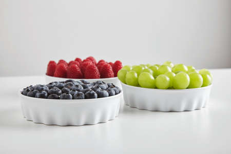 accurately: Heap of ripe raspberries and blueberries and green seedless muscat grapes accurately placed in ceramic bowls isolated on white table LANG_EVOIMAGES