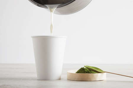 spoiling: Side view take away white paper glass and premium organic japan matcha tea on wooden table ready for modern way latte preparation. Presentation third step. Spoiling bit hot milk to glass.