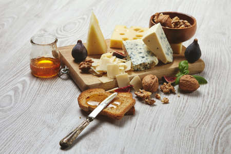 formagi: Set of four cheeses on rustic cutting board isolated on side of brushed white wooden tableServed for tasty breakfast with figs, rustic honey, dry bread and walnuts in bowl with basil leaves. Side view