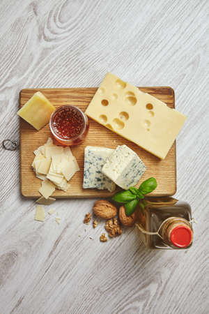 formagi: Set of four cheeses on rustic cutting board isolated on side of brushed white wooden tableServed for breakfast with extra virgin olive oil in vintage bottle, rustic honey and walnuts with basil leaves. Top view LANG_EVOIMAGES