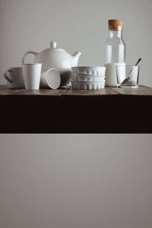 ceramic bottle: Vintage bottle closed cork with milk on aged wooden table near whiskey rox transparent glass, white ceramic plates, blank paper take away glasses, big white teapot,side view presentation isolated on white. Breakfast time LANG_EVOIMAGES