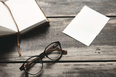 stainless steel sheet: Mysterious detective game concept. Opened notebook in leather cover, sheet of white paper and pair of stainless steel glasses isolated on black aged wood table. Side view LANG_EVOIMAGES