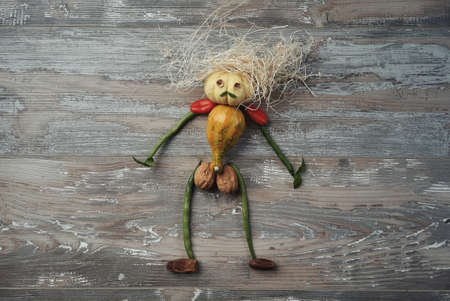 mustaches: Doll made from fresh organic vegetables in shape of brave sporty man with mustaches and mess on his pumpkin head. Fun cool concept of healthy life, isolated on vintage old wooden table