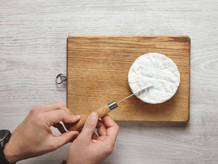 accurately: Top view brutal beautiful man hands accurately cut a triangle piece of camembert cheese with antic knife on cutting board isolated on whithe aged brushed wooden table