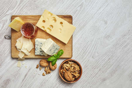 formagi: Set of four cheeses on rustic cutting board isolated on side of brushed white wooden tableServed for breakfast with rustic honey and walnuts in brown bowl with basil leaves. Top view