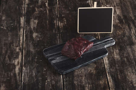 price cutting: Side view of luxury raw piece of whale meat steak on black marble stone cutting desk and aged vintage wooden table and chalk board price tag LANG_EVOIMAGES
