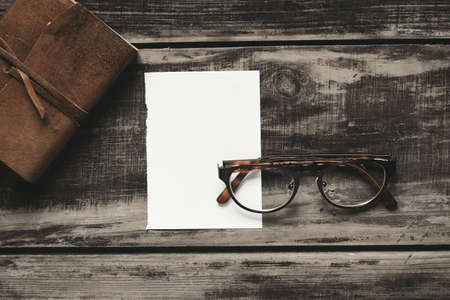 stainless steel sheet: Mysterious detective game concept. Closed notebook in leather cover, sheet of white paper and pair of stainless steel glasses isolated on black aged wood table