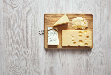 formagi: Set of four cheeses on rustic cutting board isolated on side of brushed white wooden table. Gorgonzola, Roquefort, Dor Blue, Mozzarella, Parmesan, Emmental, Gauda, Maasdam. All ready to prepare tasty italian pizza quattro quesos