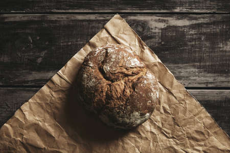 woden: Healthy rye whole grain round bread on brown craft paper isolated on black farm woden table. Home baked.