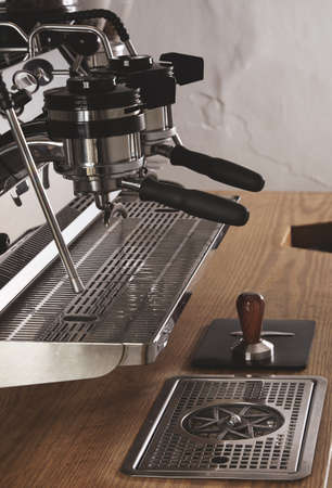 automat: Side view professional chrome coffee machine with two head and charged portafilters in cafe shop on wooden thick table and tamper on leather pad espresso, cappuccino, americano, ristretto, latte maker.