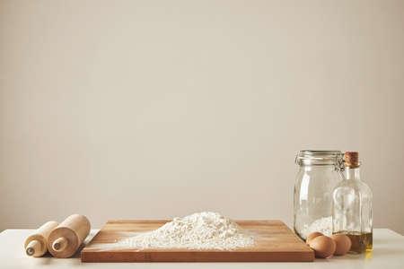 harina: Dos rodillos de amasar de madera, aceite de oliva virgen extra, tarro transparente y tabla de cortar de madera con harina blanca, huevos chiken aislados. Todo preparado para hacer la pasta LANG_EVOIMAGES