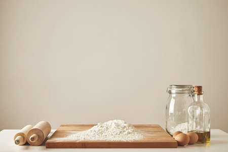 Two wooden rolling pins, extra virgin olive oil, transparent jar and wooden cutting board with white flour, chiken eggs isolated. Everything prepared for dough making