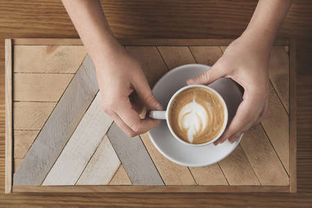 automat: Beautiful woman hands hold ceramic white with cappuccino abowe wooden plate and rustic table. Milk foam on top in tree shape. Top view in cafe shop. Sale presentation concept. LANG_EVOIMAGES