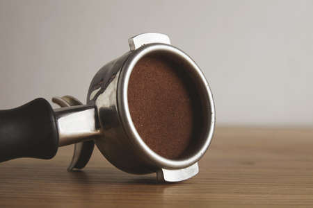 automat: Closeup on steel portafilter with ground coffee powder pressed inside. Isolated on wooden table in cafe shop. Professional coffee brewing LANG_EVOIMAGES