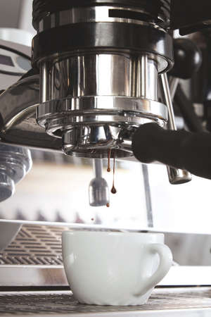 automat: Close up of espresso pouring from silver metallic coffee machine in white ceramic cup. Drops of good roasted coffee fall. Professional coffee brewing LANG_EVOIMAGES