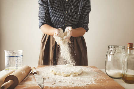 Woman adds some flour to dough on wooden table near knife, two rolling pins, measure cup, transparent jae with flour and olive oil bottle. Step by step cooking pasta dumplings guide