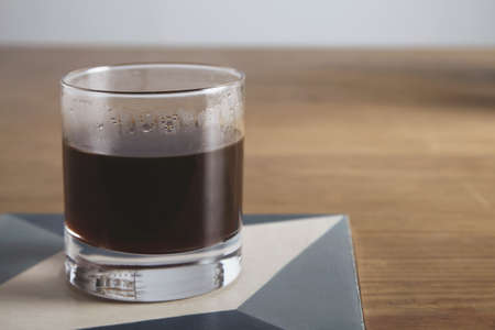 automat: Whiskey cup with hot aero pressed filtered coffee inside. Closeup, isolated on wooden table with ceramic pad in cafe shop LANG_EVOIMAGES