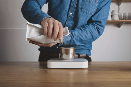 automat: Step by step aero press coffee preparation Barista in blue jeans shirt pours roasted beans from bag to steel cup on white weights Professional coffee brewing cafe shop