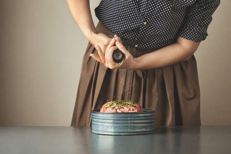 adds: Housewife adds some pepper spice in minced meat in ceramic bowl on blue table LANG_EVOIMAGES